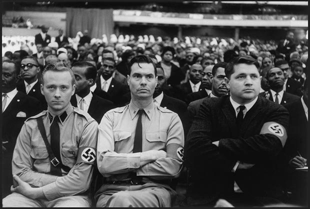 USA. Chicago. February 25th 1962. George Lincoln Rockwell, flanked by members of the American Nazi Party, listening to Malcolm X's speech at Black Muslims meeting held at the International Amphitheater.
